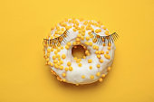 Composition with sweet tasty donut and fake eyelashes on color background