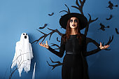 Beautiful woman dressed as witch for Halloween standing near decorated wall