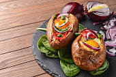 Baked sweet potato with egg and tomato on slate plate