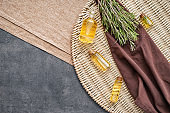 Wicker mat with bottles of fresh rosemary on table