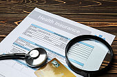 Health insurance form with magnifier, credit card and stethoscope on wooden table