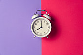 Retro alarm clock on red and purple table background, vintage lifestyle concept