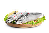 Wooden plate with tasty raw mackerel fish on white background