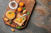 Jar of tasty tangerine jam with toasted bread on wooden board