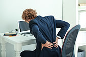 Young businessman suffering from back pain in office
