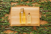 Bottles of oil and fresh rosemary on wooden table