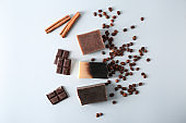 Handmade soap bars with chocolate, coffee and cinnamon on white background, top view