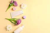 Natural cream with flowers on color background