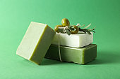 Handmade soap bars with olives on color background