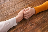 Young women holding hands on wooden background. Concept of support