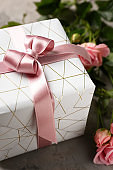 Festive gift box and flowers on grey background