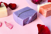 Handmade soap bars and flower petals on color background