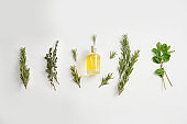 Bottle of oil with different herbs on white background