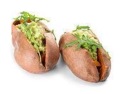 Baked sweet potato with guacamole and arugula on white background