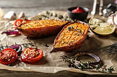 Baked sweet potato with vegetables and herbs on parchment