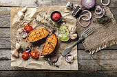Baked sweet potato with vegetables and herbs on wooden table