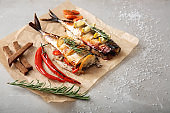Parchment with tasty mackerel fish on grey table