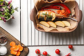 Baking dish with tasty mackerel fish and vegetables on white table
