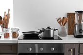 Modern electric stove and utensils in kitchen