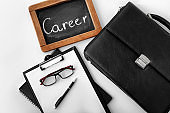 Briefcase, clipboard and chalkboard with word CAREER on white background