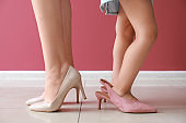 Legs of young mother with her cute little daughter wearing high-heels near color wall