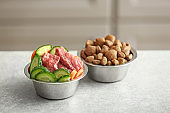 Bowls with dry and fresh pet food on table