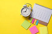 close up of calendar and alarm clock on the yellow table background, planning for business meeting or travel planning concept