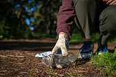 Woman collecting plastic garbage in forest