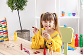 Cute little fashionista with cosmetics at home