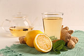Glass of tasty drink with lemon, ginger and mint on table