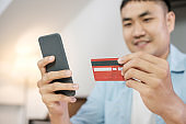 Asian man online shopping with credit card and mobile phone at home.digital lifestyle with technology