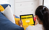 Asian woman use credit card to apply l online learning course on tablet sitting on sofa at home.digital lifestyle with technology
