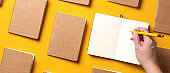 content marketing concept,.top view of hand writing on open notebook align with kraft paper book in pattern on yellow table background.mockup for advertise content online