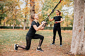 Women training with trx outside in the park.