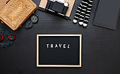 summer travel flat lay of traveller accessories set.blackboard,hat,yellow wicker bag,camera on black wooden table of influencer
