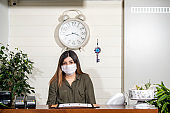 Receptionist woman protected at the reception from epidemic disease