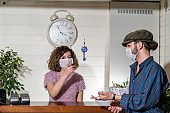 Receptionist woman and customer protected at the reception from epidemic disease