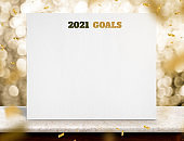 2021 goals on white paper poster on wood table with gold bokeh lights at background,mock up for adding business plan for new year