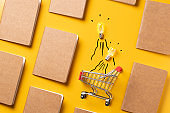 creativity content marketing concept,top view shopping cart with full of lightbulbs with Kraft paper book alignment in pattern on yellow desk surface.leave space for display your content.