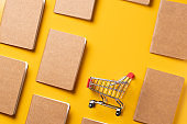 content marketing concept,top view Black and Kraft paper book alignment in pattern with shopping cart on yellow desk surface.leave space for display your content