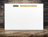 2021 new year resolutions text on white paper poster with brick wall and wood floor,Business presentation mock up for adding your list