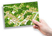 Imaginary city map with residential buildings, roads, gardens green areas and trees - green city concept image with a female hand holding a postcard