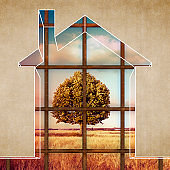The house becomes a prison - House arrest on residential building - concept image with the graphic outline of a small home closed by a metal railing towards a rural scene with a tree