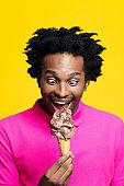 Headshot of surprised young man holding chocolate gelato