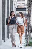 Young shopaholic friends women friends walking and carry shopping bags in the street city with happy and smiling.