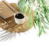 Lifestyle composition with coffee cup , notebook and eucalyptus leaves with shadows on white table  top view. copy space