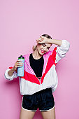 80's style portrait of smiling woman in sports clothes against pink background
