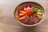 Premium fresh raw seafood mixed rice bowl (Kaisen-don/ Japanese tasty food), Japanese Rice with sashimi of tuna, Maguro, Otoro, salmon, squid and ikura (Salmon eggs) on wood background