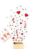 Valentine's day background.  gift box with various party confetti, red hearts and decoration isolated on white background top view.