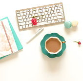 Flat lay women's office desk. Female workspace with laptop, flowers roses,  accessories, notebooks, cup of coffee on white background. Top view feminine background.